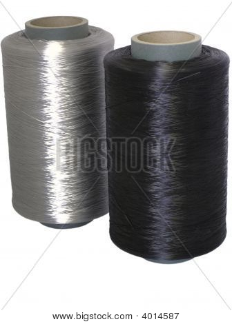 Two Bobbin With White And Black Thread.
