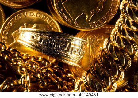 Greek meander ring Jewels and gold coins over dark background