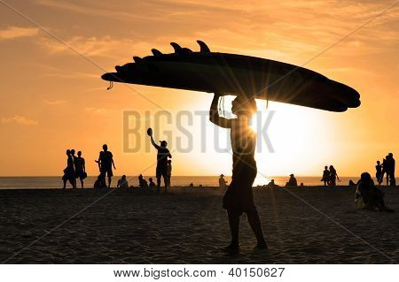Kuta Beach at sunset with man carrying surfboards
