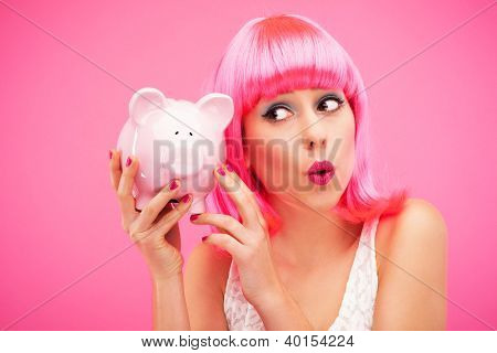 Attractive woman holding piggy bank