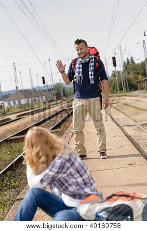 Man waving to woman sitting on railroad vacation travel backpack