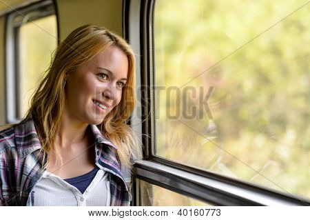 Happy woman looking out train window pensive vacation traveling tourist