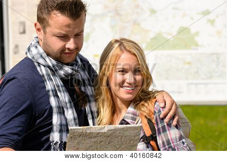 Couple together on holiday with map happy tourists directions trip