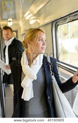 Man watching woman looking out the window train travel commuting