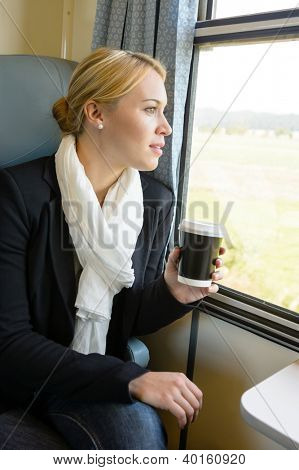 Woman looking out the train window pensive commuter coffee trip