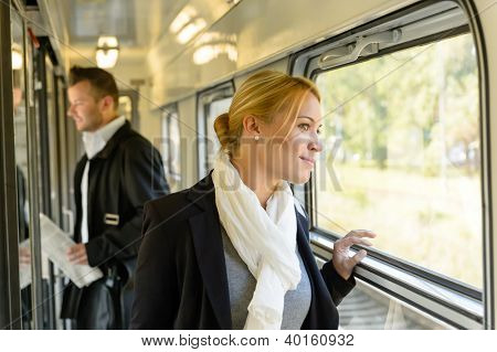 Woman looking out the train window traveling smiling commuter pensive
