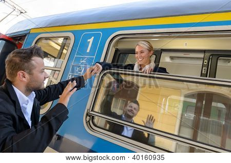 Man saying goodbye to woman on train smiling window commuter