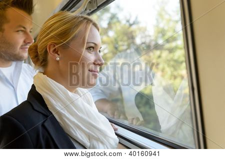 Woman man looking out the train window smiling thinking friends