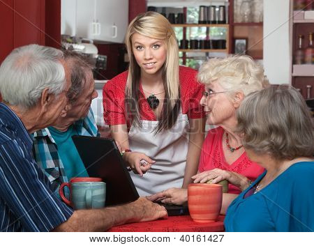 Seniors With Laptop And Helpful Waitress