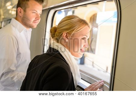 Man and woman looking out train window smiling travel commuters