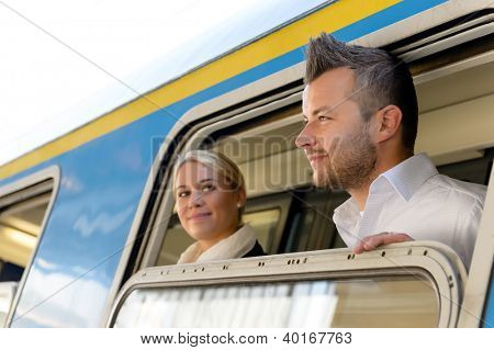 Man and woman looking out train window smiling commuters journey