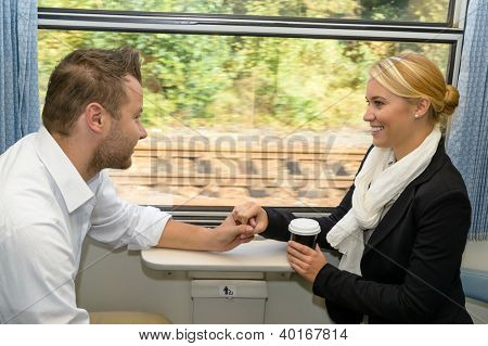 Woman and man on train holding hands sympathy friends commuters