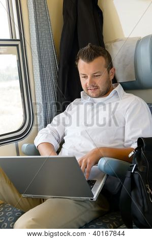 Man sitting in train using laptop computer commuting from work