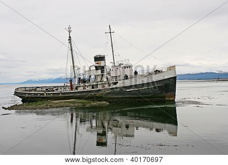 Old boat from Ushuaia, with lake reflection