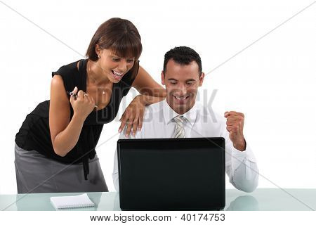 Excited business duo with laptop