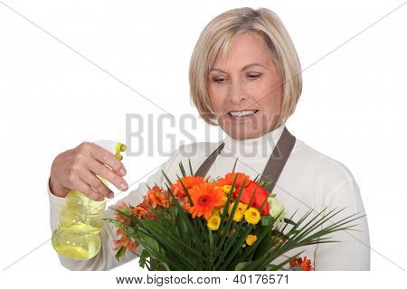 Senior female florist spraying water on bouquet
