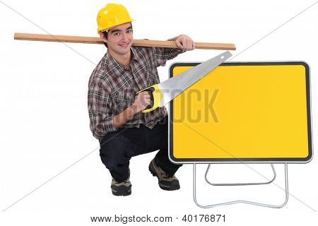 carpenter holding plank over shoulder and handsaw