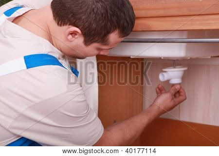 Plumber placing siphon