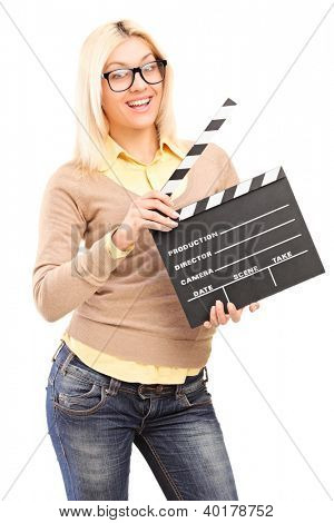 A smiling blond female holding a movie clap isolated on white background