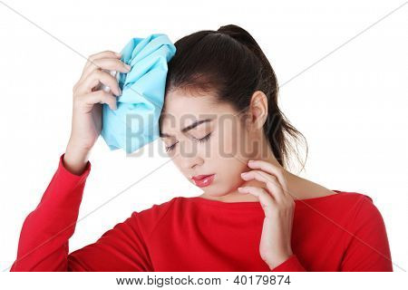 Woman with ice bag for headaches and migraines , isolated on white