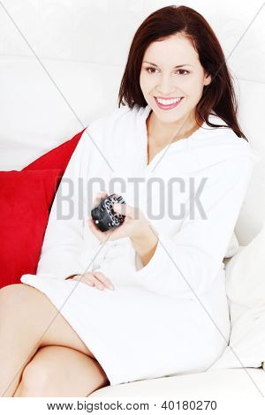Portrait of a young beautiful smiling woman dressed in a bathrobe, sitting on a couch near two red pillows, holding a remote control and watching tv.