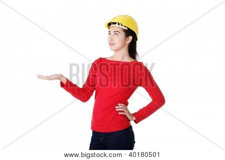 Young woman worker in yellow helmet presenting copy space on her palm