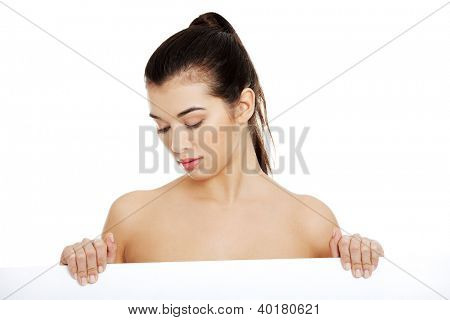Sexy naked brunette holding empty board , isolated on white.