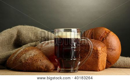 tankard of kvass and rye breads, on wooden table on grey background