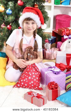 Little girl in Santa hat near the Christmas tree in festively decorated room
