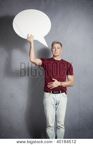 Disappointed man holding white blank speech bubble with space for text isolated on grey background.