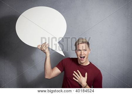 Amazing news: Surprised handsome man holding white blank speech balloon with space for text isolated on grey background.