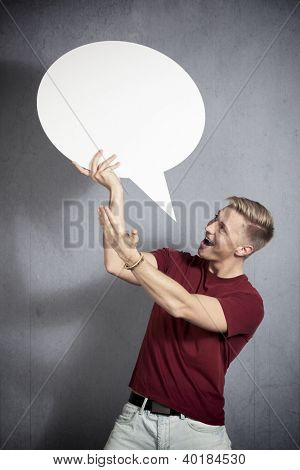 Great idea: Astonished laughing man presenting white blank speech bubble with space for text, isolated on grey background.