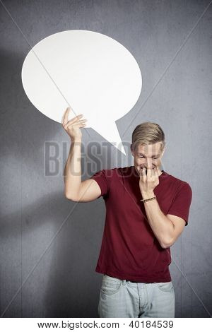 Concerned man holding white blank speech bubble with space for text isolated on grey background.