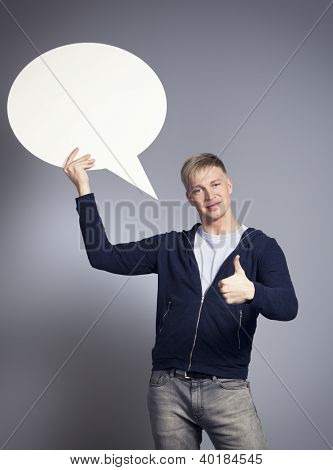 Smiling man giving thumbs up while holding white blank speech balloon with space for text isolated on grey background.