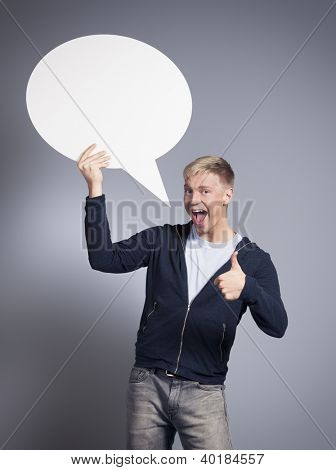 Great idea: Cheerful man giving thumbs up while holding white empty speech bubble with space for text isolated on grey background.