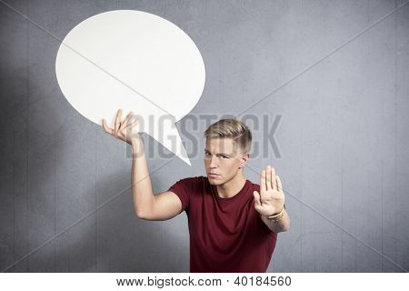 Serious man showing stop gesture with hand as warning while holding white empty speech balloon with space for text isolated on grey background.