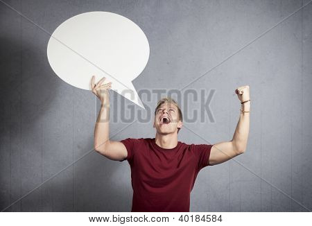 Brilliant news: Successful joyful man shouting while holding white empty speech balloon with space for text isolated on grey background.