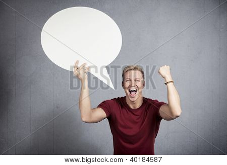 Fantastic news: Shouting man being happy about success while holding white blank speech bubble with space for text isolated on grey background.