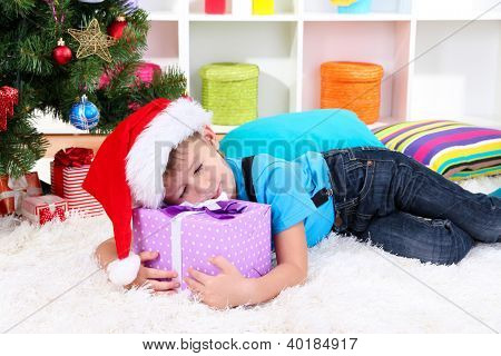 Little boy  fell asleep with gift in his hands under the Christmas Tree waiting for Santa Claus to come