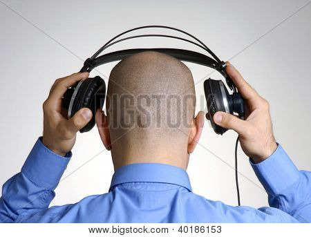 Rear view from an adult bald head man placing and using headphones.