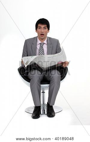 A dumbfounded businessman reading the newspaper.