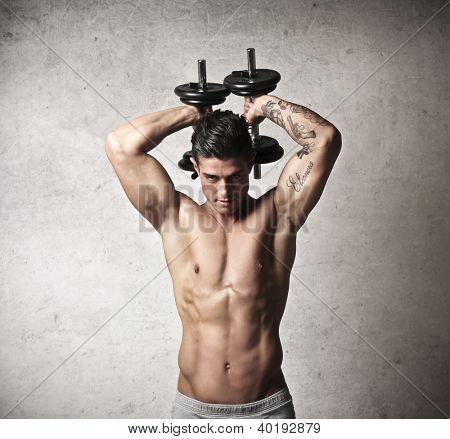 Muscular man raising behind his head two dumbbells