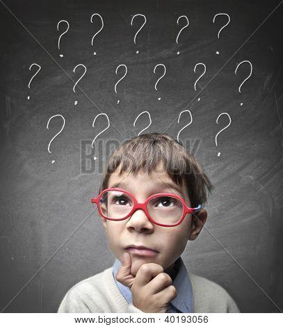 Niño con muchos signos de interrogación