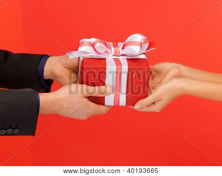 closeup picture of man and woman's hands with gift box