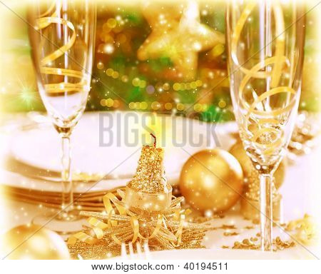 Photo of romantic holiday dinner, traditional adorned Christmas tree, two glasses for champagne, luxury white utensil decorated with golden baubles and candles, restaurant table setting