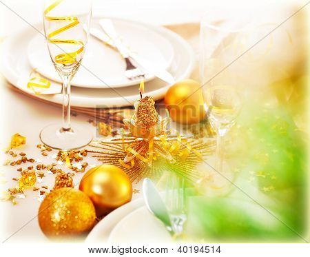 Picture of New Year table decorations, luxury festive table setting, romantic holiday dinner, white utensil adorned with golden shiny baubles, glasses for traditional Christmastime drink, champagne