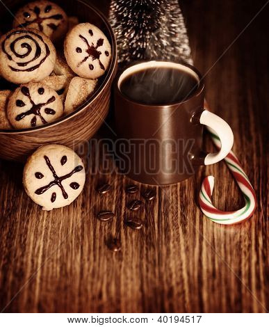 Picture of traditional Christmas sweets with cup of hot chocolate on wooden table, New Year dessert, roasted brown coffee bean, candy cane, little decorative festive pine tree, homemade cookies