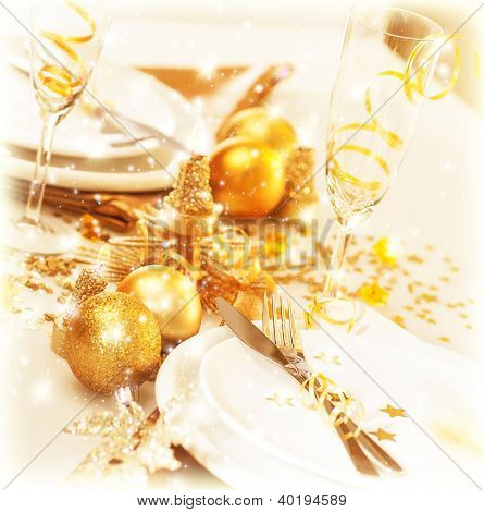 Picture of luxury festive table setting, beautiful white utensil decorated with golden balls and candles, elegant plate served with cutlery, Christmas home interior, New Year dinner
