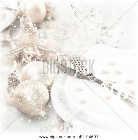 Photo of luxury festive table setting, beautiful white dishware decorated with silver baubles and candles, elegant plate served with knife and fork, Christmastime home interior, New Year dinner