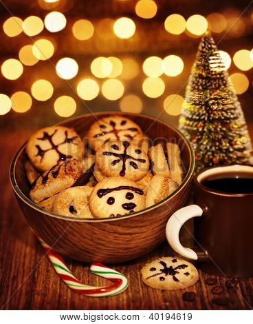 Picture of Christmastime gingerbread with cup of coffee on wooden table, New Year sweets still life on dark glowing brown background, little decorative Christmas tree, candy cane